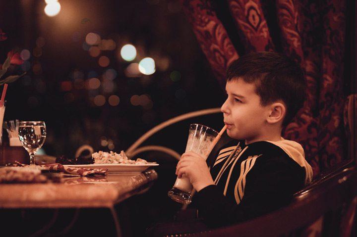 boy drinking milkshake at restaurant