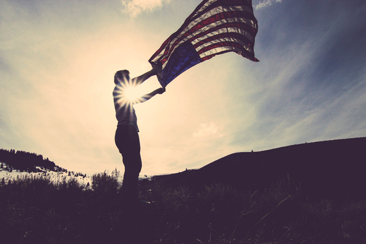 person waving a large American flag in the wind at sundown - veterans day