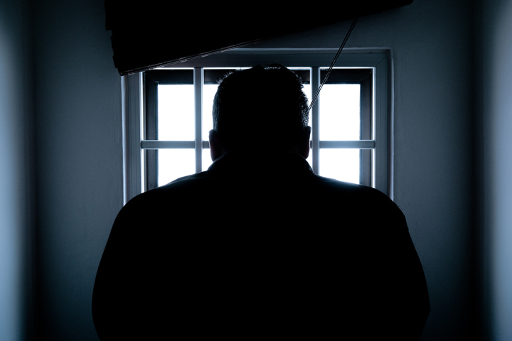 man standing in front of window in jail cell - incarceration