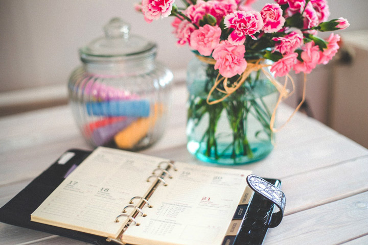 daily planner open on table near vase of pink flowers - #14days