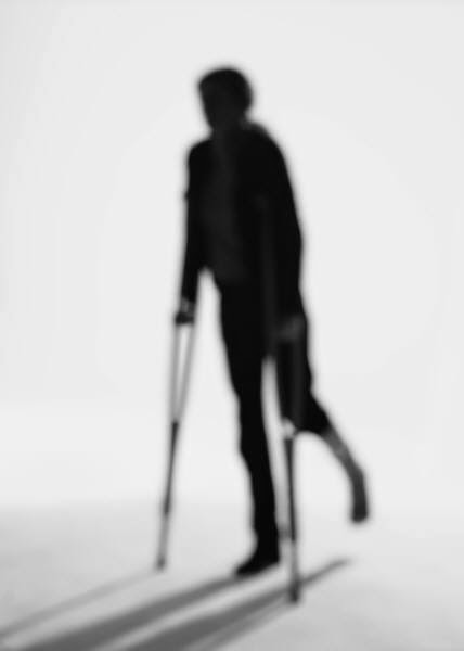 silhouette of person on crutches