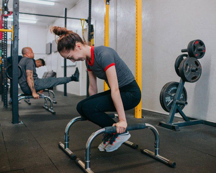 woman exercising at weight lifting gym - meth
