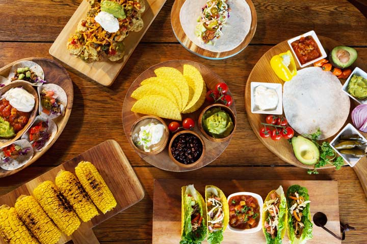 tacos and taco fixings set out on a table - food