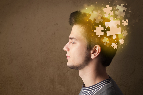 profile of man with puzzle pieces coming out of head
