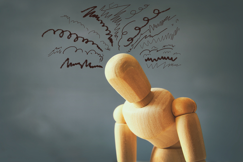 wooden man with squiggles over head