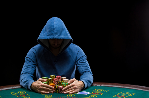 hooded man sitting at poker table with stacks of chips