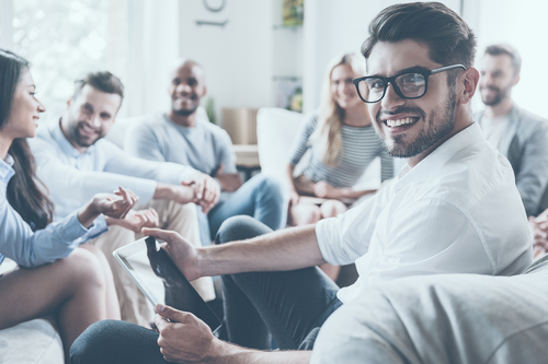 smiling man at group therapy meeting
