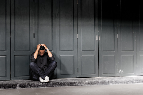upset man sitting on ground outside of building