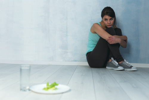 girl in corner afraid to eat even lettuce and water