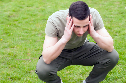 stressed man squatting with hands on head
