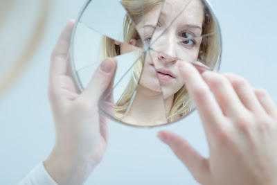 woman looking into broken mirror