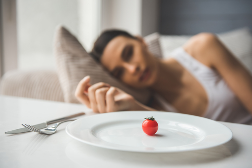 woman looking at plate with one small tomato on it
