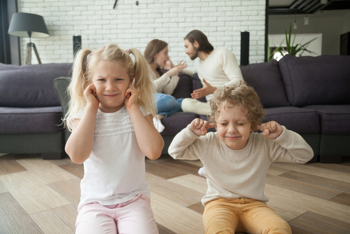 kids covering ears while parents argue
