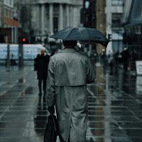 people walking in rain on busy street