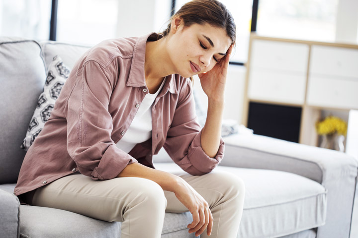 young woman on couch not feeling well