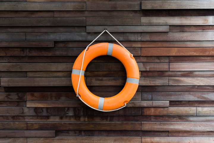 image of life saver ring hanging on wooden wall