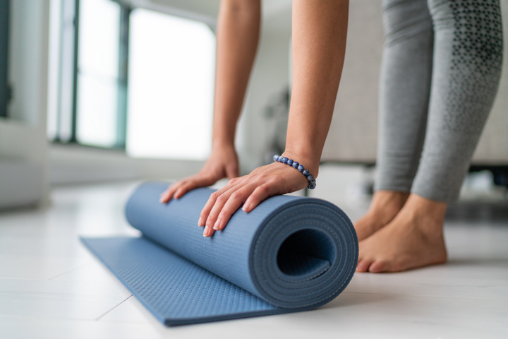 woman rolling up yoga mat - yoga teacher