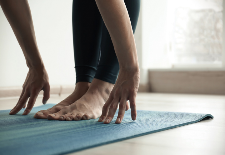 close up of hands and feet of person standing and stretching on yoga mat - through yoga