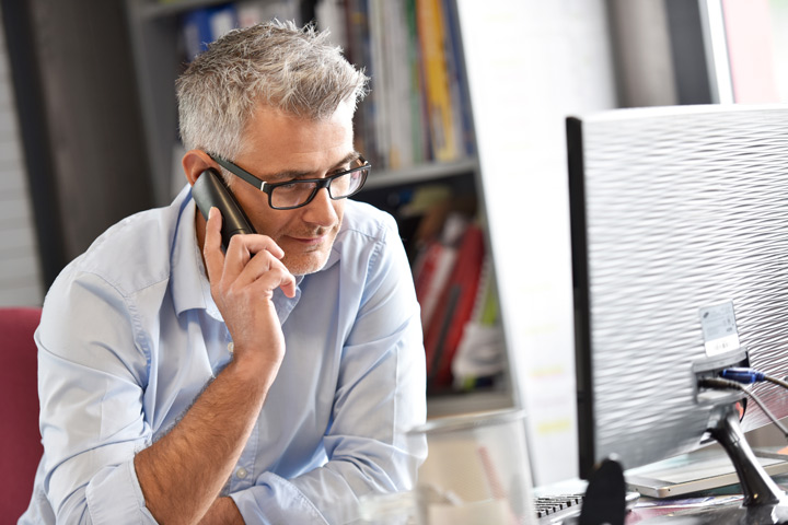 handsome senior man with glasses on the phone in his office - insurance
