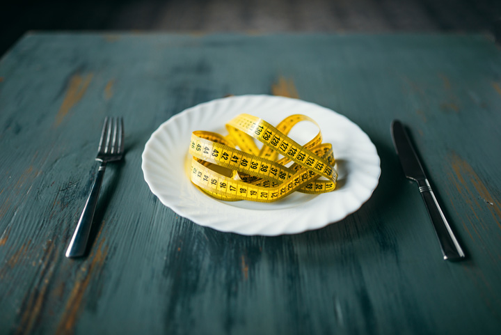 white plate with yellow tape measure on it, set on table with fork and knife - depression and eating disorders