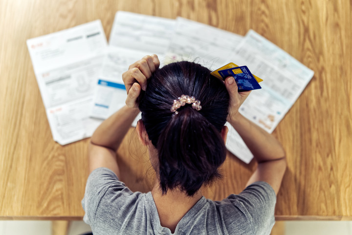 stressed woman holding credit cards and looking down at statements - compulsive shopping
