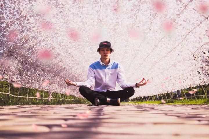 young man meditating in lotus position - meditation