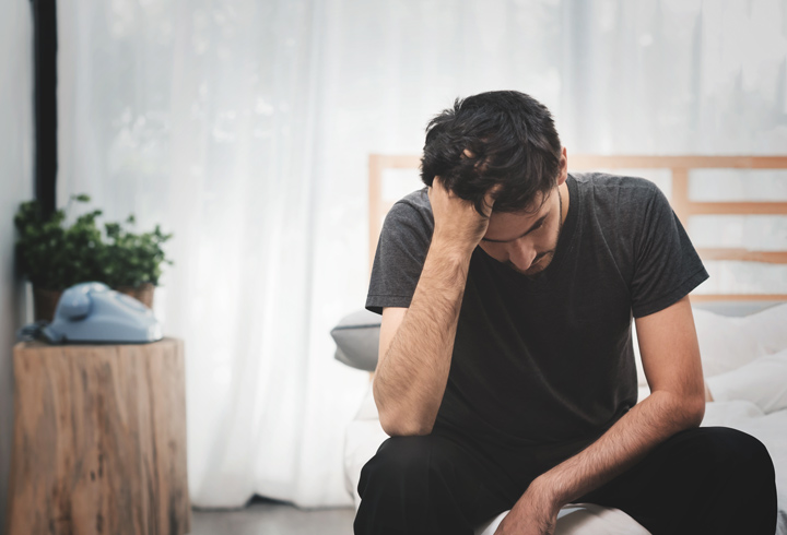 man sitting on the edge of his bed with hand in his hair looking stressed - anxiety and addiction