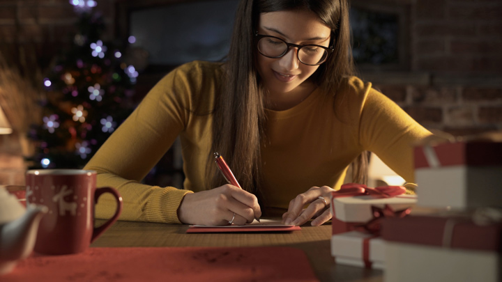 smiling woman writing notes or Christmas cards - holiday traditions