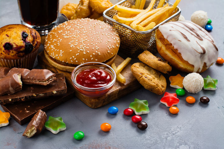 junk food on table - burger, fries, donuts, candy, etc. - food addiction
