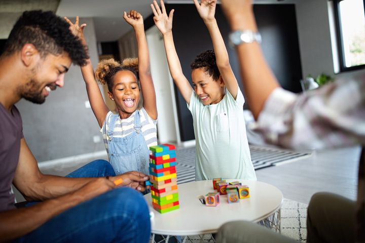 young family playing games at home - parents
