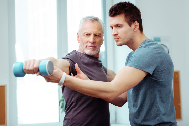 therapist helping man do exercises at physical therapy - pain management