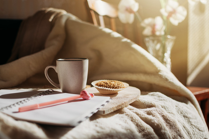 coffee, muffin, and journal sitting on bed in morning - establishing routines