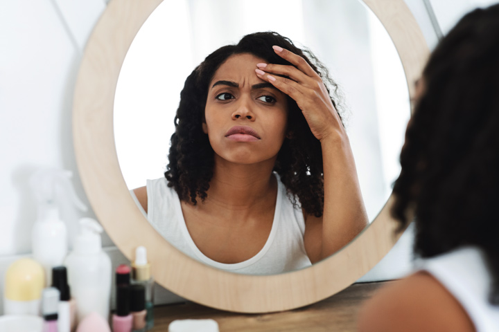 pretty African American woman looking in mirror at her face - body dysmorphia