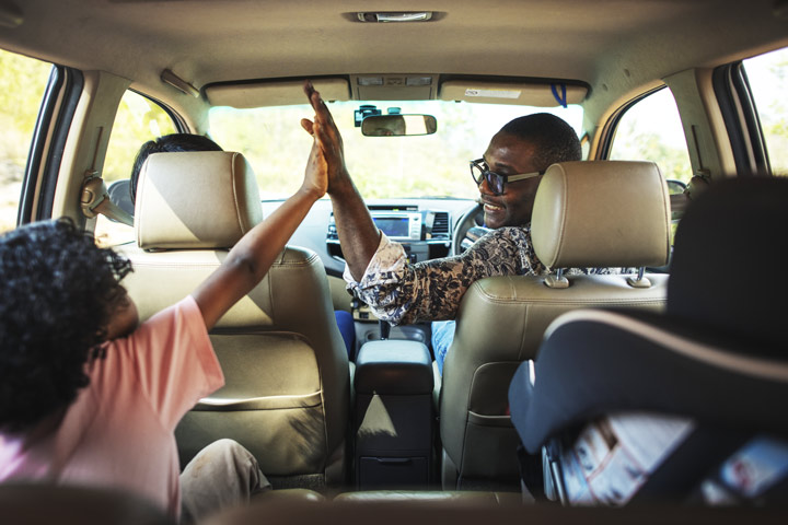 Black Dad in front seat of car high-fiving his daughter in the backseat - holiday season road trip