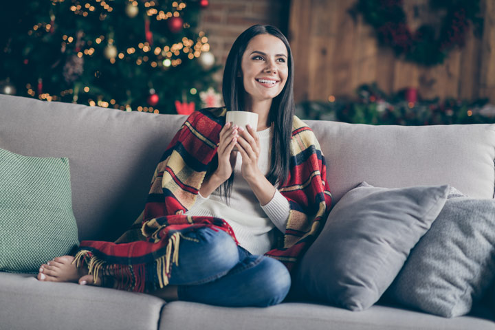 pretty dark haired woman smiling while sitting on couch in room with Christmas tree - holiday season