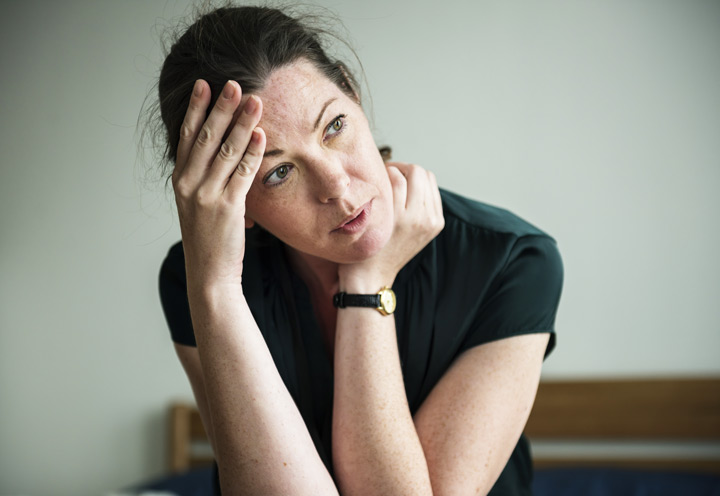 woman looking stressed, with hand on head, thinking - willpower