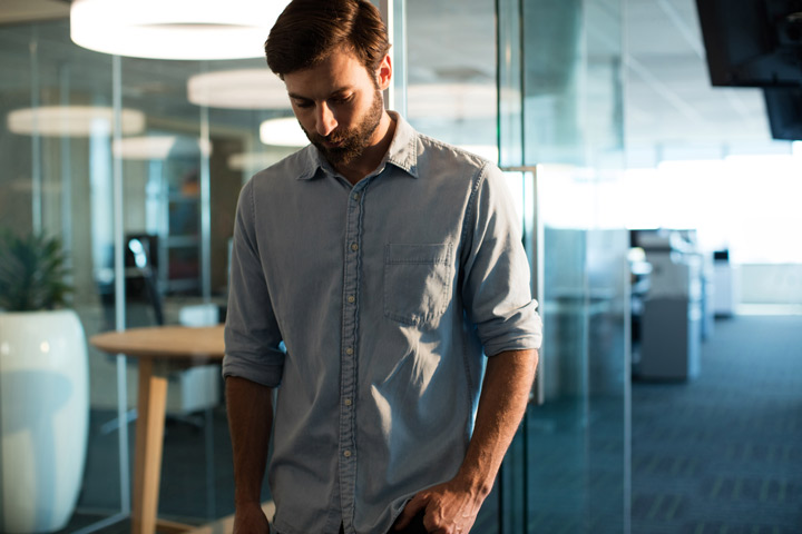 attractive young man at office looking depressed - causes of depression