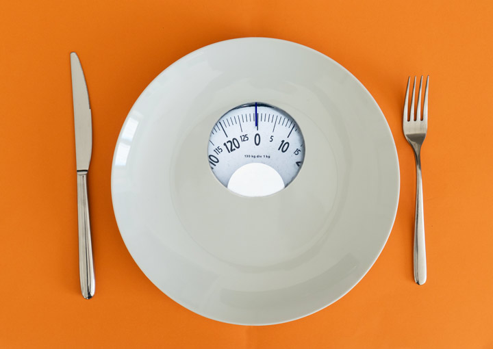 plate that is also scales as place setting on an orange table - anorexia nervosa