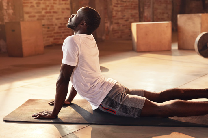 young Black man doing yoga on mat - thoughts and emotions