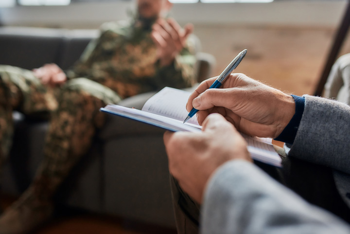 cropped shot of man in military fatigues talking to a therapist who is taking notes - treatment for veterans