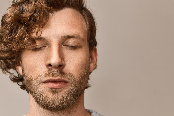 closeup of handsome man in his late twenties with his eyes closed - urge surfing