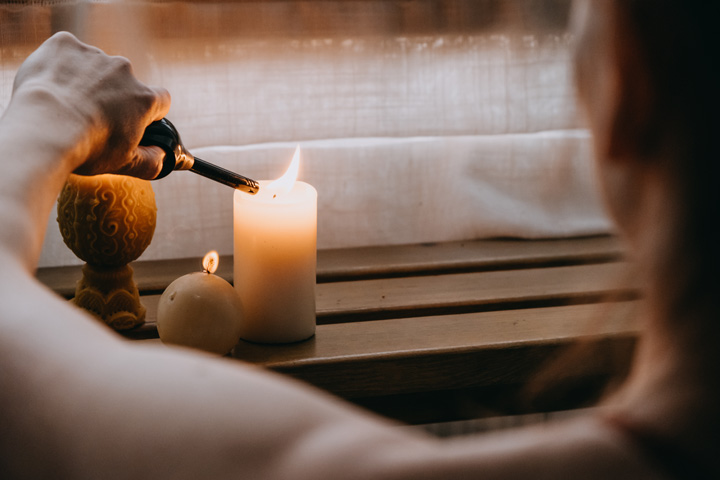 cropped shot of person lighting several candles - self-care